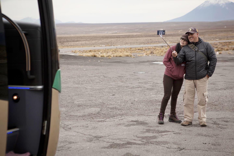 Turista tomando fotos con el volcán Misti detrás visitado con Bus 4M Express Perú